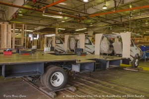 """Early in the production cycle Coachmen Class C RVs have had their floors installed and under-floor compartments hung. Note that they sit on wheeled platforms. When ready for the next stage """"3 burly guys""""push them down the line."""